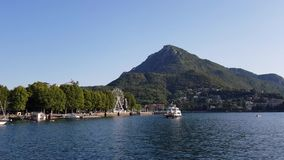Ferry in the lake of Lecco with the ferris wheel in the trees on a beautiful summer day. Italy stock video