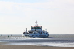 Ferry leaves dutch Ameland Island through fairway Royalty Free Stock Photos