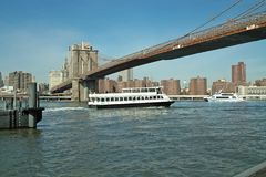 Ferry under the Brooklyn Bridge, New York, USA. Ferry leaves Fulton Landing under the Brooklyn Bridge, going up the East River Stock Photos