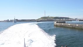 Ferry leaving harbor on Helgoland island on clear summer day stock video