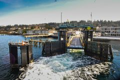 Ferry Leaving From The Mukilteo Terminal to Whidbey Island On A Beautiful Winter Sunny Morning. Leaving behind a wake of waves through the pillars at the gate Royalty Free Stock Photo