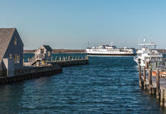 Ferry leaving Woods Hole for Martha's Vineyard, with view of dock. Car ferry leaving Woods Hole for Martha's Vineyard, docks in foreground Royalty Free Stock Image