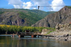 Ferry through the Little Yenisei river near small village. Royalty Free Stock Photos