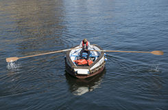 Ferry with man using oars to row Royalty Free Stock Image