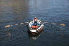Ferry with man using oars to row Royalty Free Stock Images
