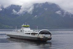 Ferry on the Norwegian fjord over the mountain slopes stock photography