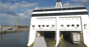 Ferry With Open Door To Take Automobile Traffic. Two big trucks boarding in the ferry across open door stock footage