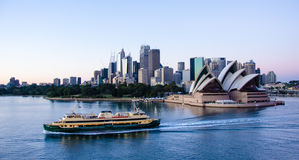 Ferry passes in front of Sidney Opera House with the city in the background. SIDNEY, AUSTRALIA NOVEMBER 2, 2016 A passenger ferry passes in front of the Sidney Royalty Free Stock Photo