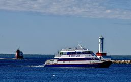 A Ferry Passes Between Round Island Lighthouse. This is a early morning Spring picture of a ferry passing between the iconic Round Island Lighthouse and the royalty free stock image
