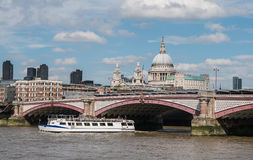 Ferry passes under Blackfriars Bridge on Thames with St. Paul's Royalty Free Stock Photos