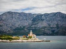 Ferry passing close to Sucuraj lighthouse on Hvar island, Croatia stock photography