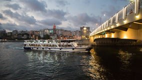 Ferry passing under the Galata bridge at night. Golden Horn. Turkey, Istanbul. Stock Photography