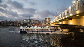 Ferry passing under the Galata bridge at night. Golden Horn. Turkey, Istanbul. Stock Photos