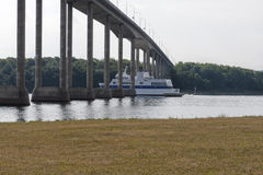 Ferry Passing Underneath a Bridge Stock Photo
