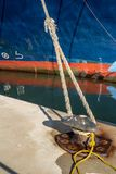 Ferry rope tied to metal boat slip at dock. Olbia royalty free stock images