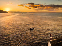 A ferry and a sailing boat leave the port on a golden morning under the safety of the port wall and light. Royalty Free Stock Photos