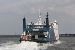 Ferry sails into the harbor of Harlingen Stock Photo