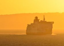 Ferry Ship in Haze. A ship, which is a ferry or perhaps small cruise ship, during a hazy sunset off the Straits of Dover, England Royalty Free Stock Photography