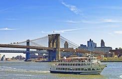 Ferry vicino al ponte di Manhattan e del ponte di Brooklyn sopra East River Fotografia Stock