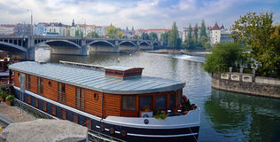 Ferry on Vltava river , Prague. View on Vltava river, Jiraskuv bridge and ferry boat hotel Stock Image