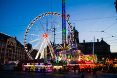 Ferry wheel and flying swings on Dam square in Amsterdam at night, Netherlands Royalty Free Stock Images