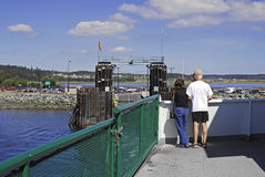 Ferryboat docking. A couple watching from on deck as a ferryboat approaches a dock Royalty Free Stock Photography