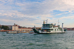 Ferryboat Metamauco and motor boats in Grand Canal in Venice. Venice, Italy - August 21, 2015: Ferryboat Metamauco (IMO 9198434) and motor boats in Grand Canal Royalty Free Stock Photos