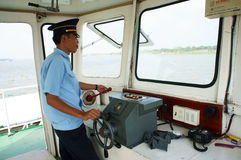 Ferryman controlestuurwiel in de veerboot van de cabine. DONG THAP, VIETNAM 27 JANUARI Stock Foto
