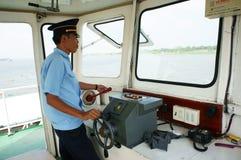 Ferrymankontrollstyrningen rullar in kabinens färja. DONG THAP VIETNAM JANUARI 27 Arkivfoto