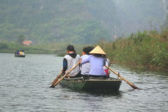 Ferrymen are taking tourists to visit the Trang An Eco-Tourism Complex, a complex beauty - landscapes called as an outdoor. NINH BINH, VIETNAM - MARCH 29, 2010 royalty free stock photography