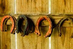 Fers à cheval accrochant sur des clous dans un mur en bois image libre de droits