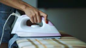 Fers de femme avec du fer à repasser blanc et rose sur le bureau banque de vidéos