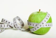Fersh grüner Apfel mit messendem Band stockfotografie