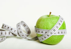 Fersh green apple with measuring tape. Fresh green apple with measuring tape on white background Stock Photography
