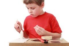 Fertigkeiten des kleinen Jungen am kleinen Tisch Stockfoto