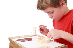 Fertigkeiten des kleinen Jungen am kleinen Tisch, Seitenansicht Stockbild