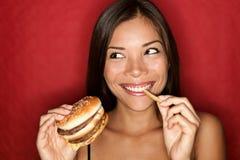 Fertigkostfrau, die Burger isst lizenzfreies stockfoto