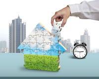 Fertigungszusammenbauende Hausformpuzzlespiele mit Wecker Lizenzfreies Stockfoto