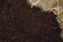 Fertile garden soil texture with jute cloth background top view Stock Images