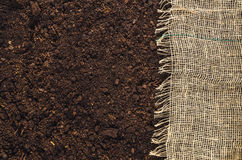 Fertile garden soil texture with jute cloth background top view Stock Photos
