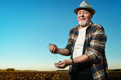 Fertile land. An elderly farmer standing in a plowed field. Agriculture, crop concept stock images