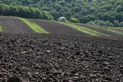 Fertile soil. Freshly ploughed field with green rolling hills in the distance stock photos