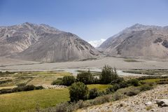 Fertile Wakhan Valley with Panj river near Vrang in Tajikistan. The mountains in the background are the Hindu Kush in Afghanistan. Central asia stock photo