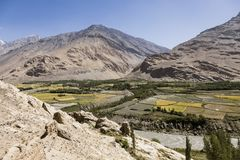 Fertile Wakhan Valley with Panj river near Vrang in Tajikistan. The mountains in the background are the Hindu Kush in Afghanistan. Central asia stock photography