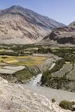 Fertile Wakhan Valley with Panj river near Vrang in Tajikistan. The mountains in the background are the Hindu Kush in Afghanistan. Central asia royalty free stock image