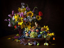 Fertility. Autumn still life with sunflowers flowers fruit grapes pears apples peaches plums blackberries Physalis asters stock images