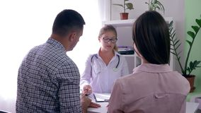 Fertility clinic, female gynecologist tells about the of health of woman to a young couple. Fertility clinic, female gynecologist tells about the of health of a stock video footage