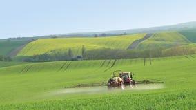 Fertilizante de rociadura del tractor en campo de la primavera almacen de video