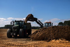 Fertilize the field, excavator with shovel fills manure in the t. Fertilize the field, excavator with shovel fills organic fertilizer or manure in the trailer of royalty free stock photography