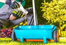 Fertilize o relvado pelo jardineiro foto de stock